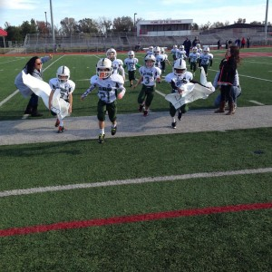 The South Highlands Second Grade Tigers run through a banner before their Souper Bowl game.